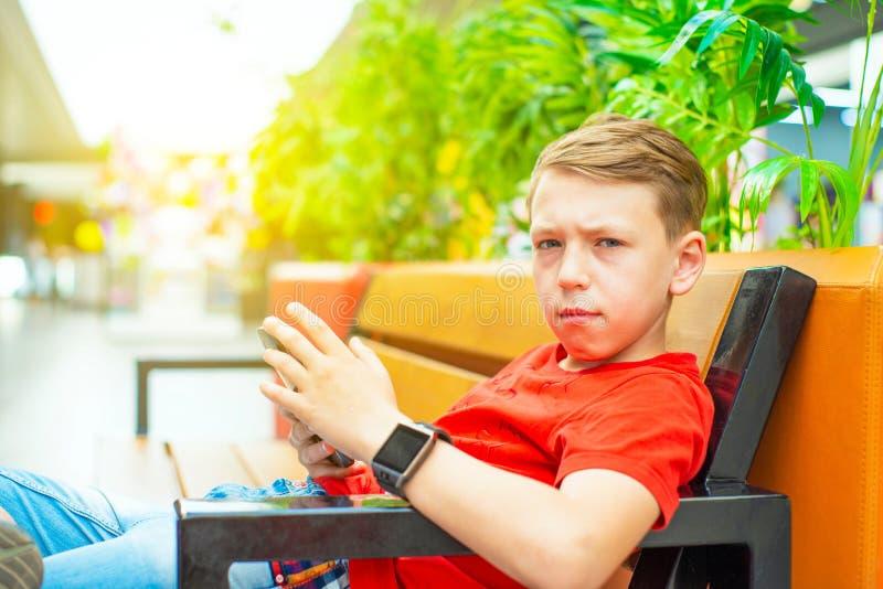 Un garçon avec un smartphone s'assied sur un banc et écrit et lit un message et regarde l'appareil-photo Photo avec la teinture images stock