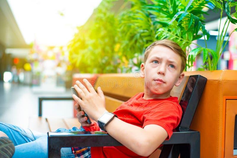 Un garçon avec un smartphone s'assied sur un banc et écrit et lit un message et regarde loin Photo avec la teinture photos stock