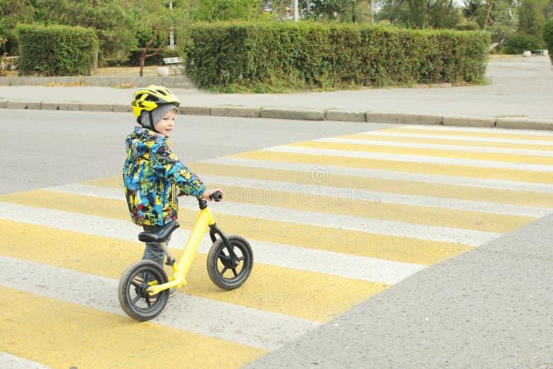 Un garçon avec une bicyclette croise un passage pour piétons avec les taches jaunes images stock