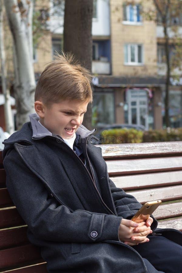 Un garçon avec une expression irritée dans un costume d'affaires est assis sur un banc avec un smartphone Il n'aime pas ce qu'il  photographie stock