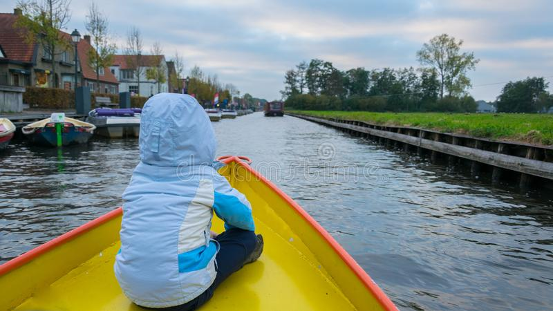 Un garçon avec une veste bleue avec le sien de retour sur l'avant du bateau sur les canaux de l'eau dans Giethoorn, Pays-Bas, pl photo stock
