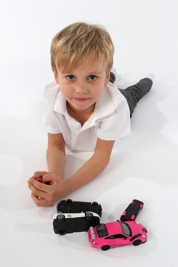 Un garçon beau de petit enfant se trouvant sur le plancher avec un groupe de jouets de voiture images stock