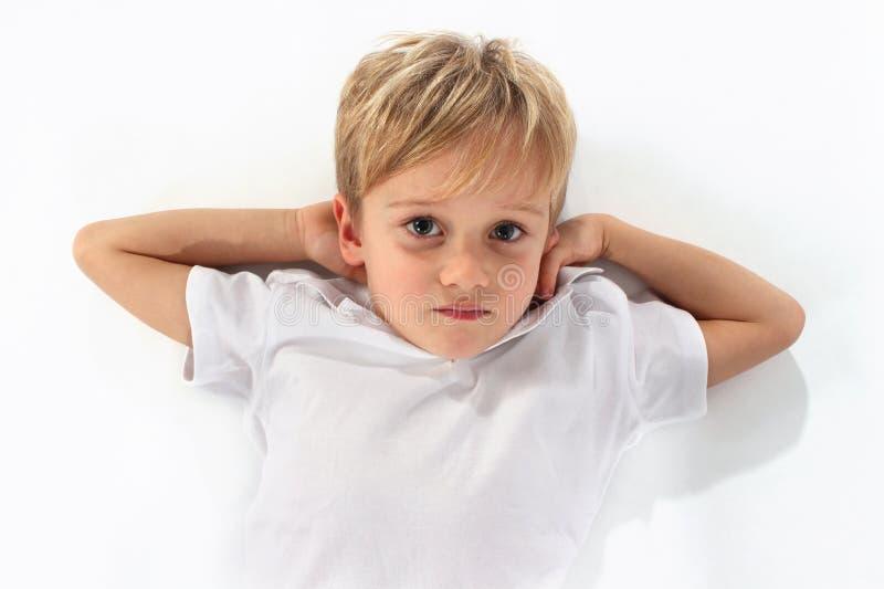 Un garçon beau se trouvant sur le plancher avec ses bras sous sa tête photographie stock