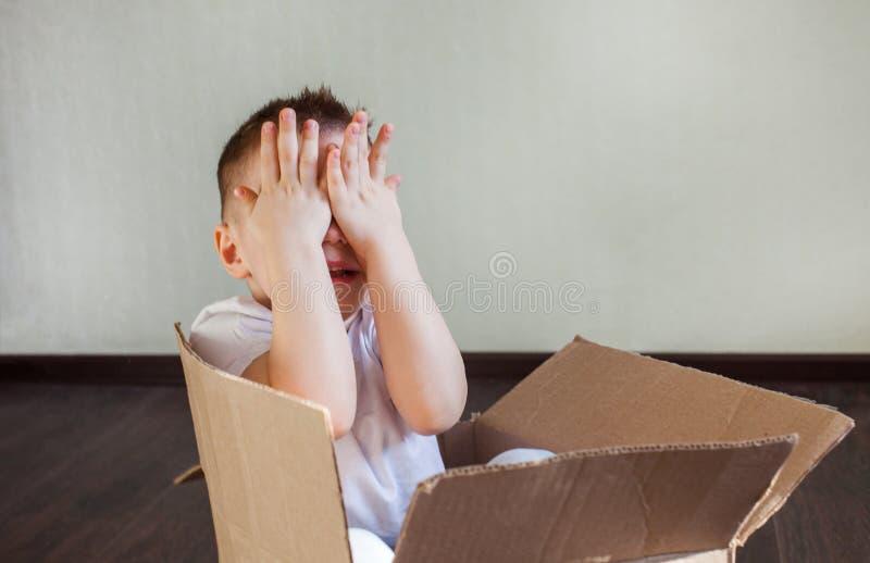 Un garçon blond de 4 ans s'assied dans une boîte en carton à la maison et joue le cache-cache, sélectionnent un huer photo stock