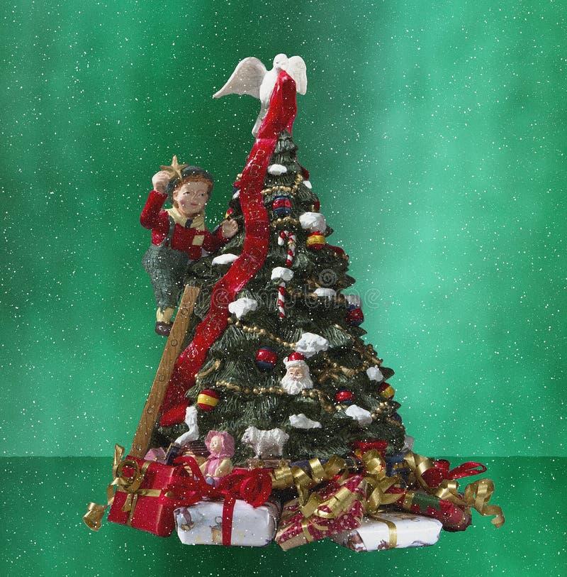 Un garçon décorant un arbre de christamas photo stock