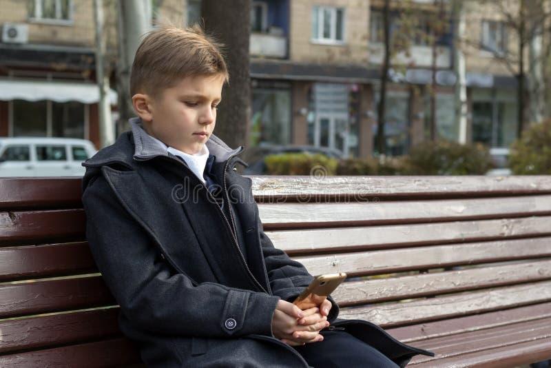 Un garçon d'âge scolaire assis sur un banc dans un parc dans un beau manteau d'affaires et regardant quelque chose sur son smartp photo libre de droits