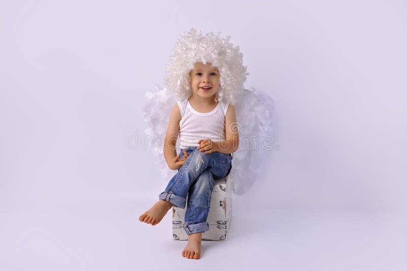 Un garçon d'ange avec des ailes dans la perruque blanche image stock