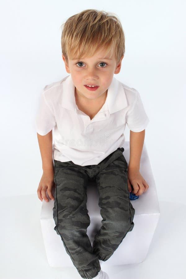 Un garçon d'enfant reposant un bloc avec une attitude mignonne innocente photo libre de droits