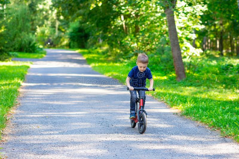 Un garçon dans la forêt monte sur le vélo d'équilibre Jeunes adultes image libre de droits