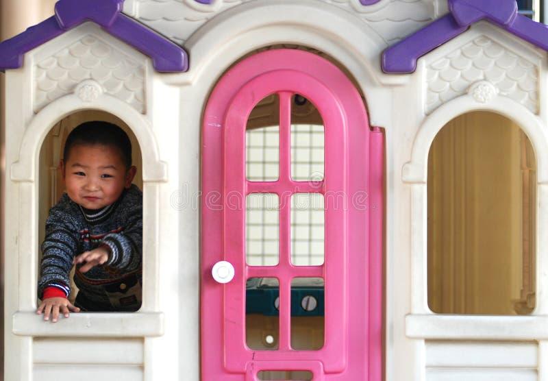 Un garçon dans la maison de poupée photo stock