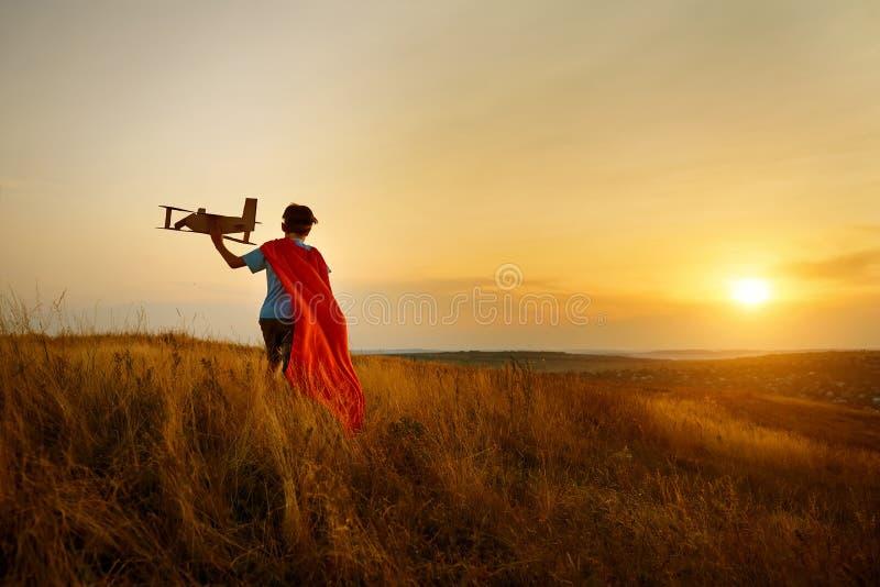 Un garçon dans le costume du pilote marchant sur le champ au coucher du soleil photos libres de droits