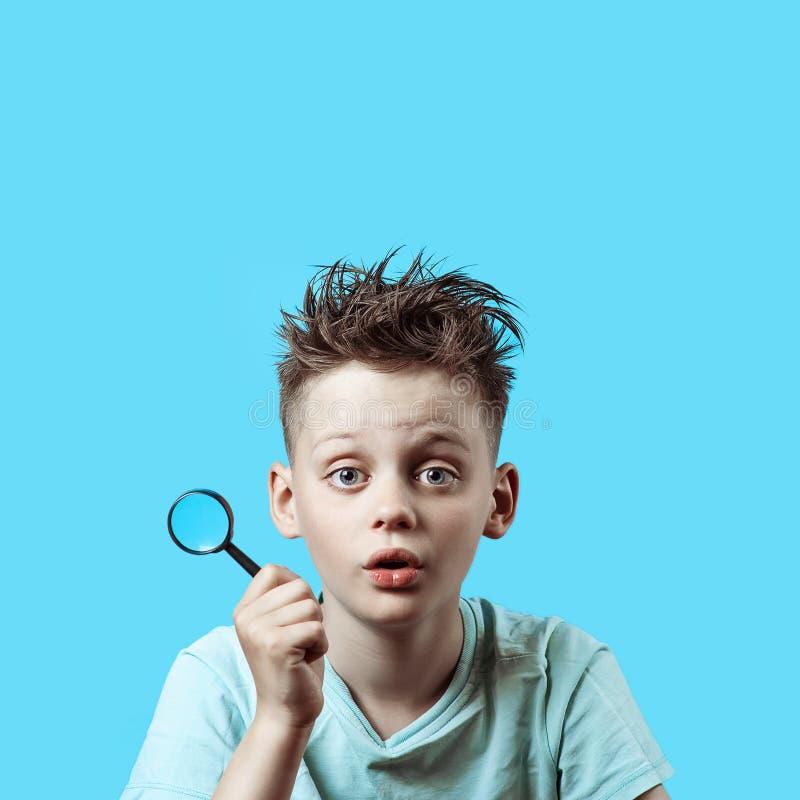 Un garçon dans un T-shirt léger tenant une petite loupe sur le fond bleu photographie stock