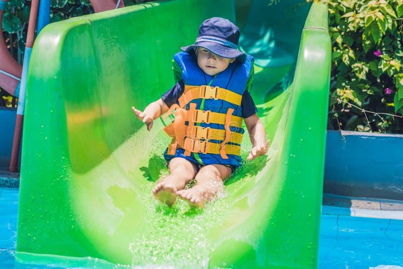 Un garçon dans un gilet de sauvetage glisse vers le bas d'une glissière dans un parc aquatique image libre de droits