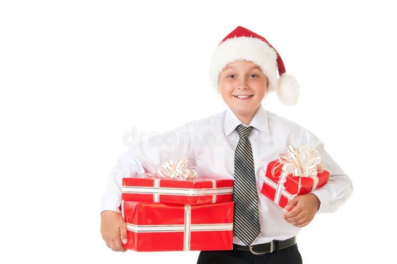Un garçon dans une chemise blanche et un chapeau de Santa Claus de nouvelle année avec les cadeaux rouges Fond blanc d'isolement photos stock