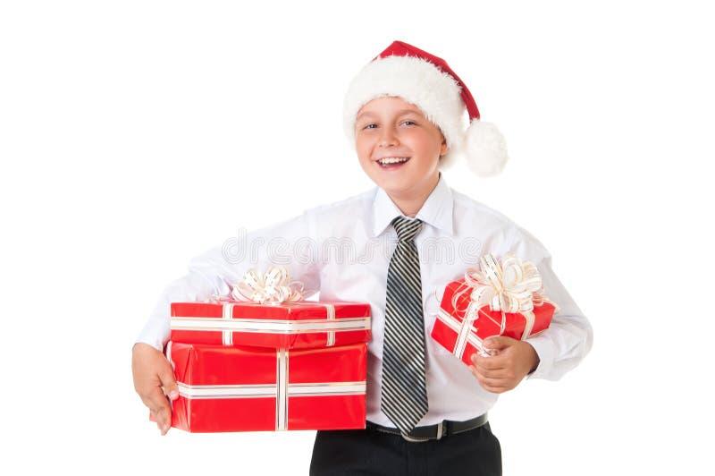 Un garçon dans une chemise blanche et un chapeau de Santa Claus de nouvelle année avec les cadeaux rouges Fond blanc d'isolement photo libre de droits