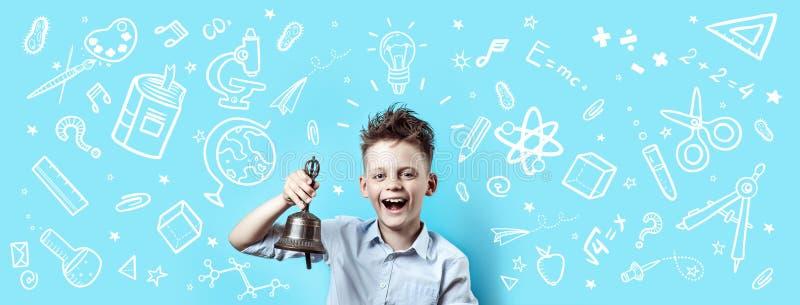 Un garçon dans une chemise légère sourit et sonne une cloche Autour ce sont de diverses icônes d'école sur le fond bleu photos stock