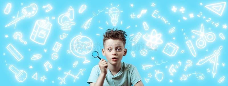 Un garçon dans une chemise légère tenant une loupe Autour ce sont de diverses icônes d'école sur le fond bleu photos stock