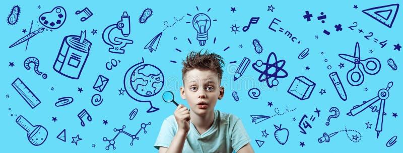 Un garçon dans une chemise légère tenant une loupe Autour ce sont de diverses icônes d'école sur le fond bleu image stock