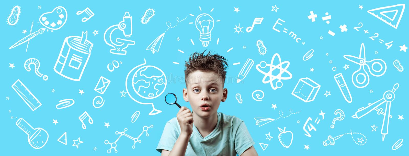 Un garçon dans une chemise légère tenant une loupe Autour ce sont de diverses icônes d'école sur le fond bleu images libres de droits