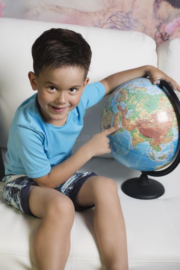 Un garçon de 5-6 ans avec un globe photo stock