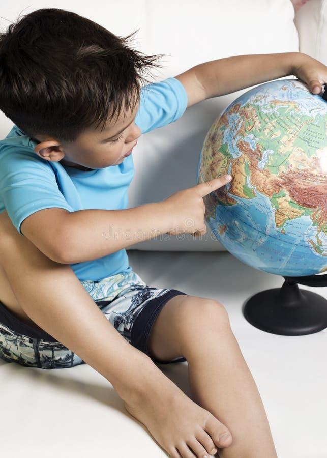 Un garçon de 5-6 ans avec un globe photographie stock