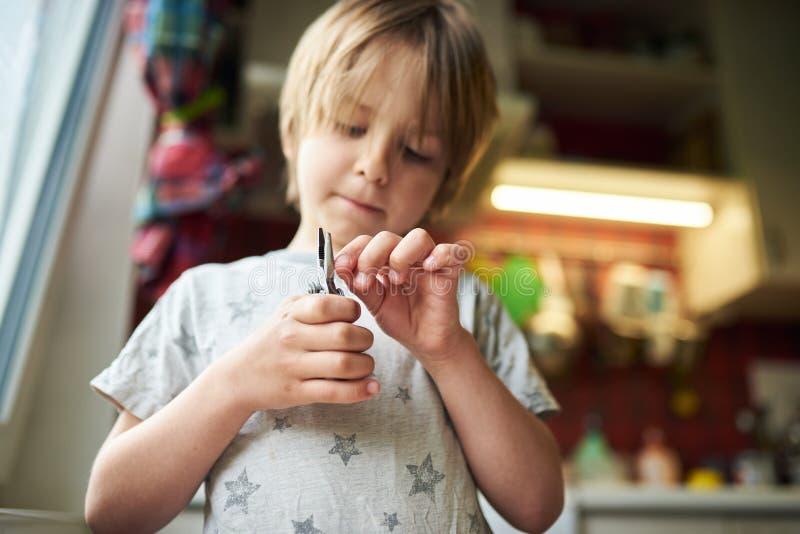 Un garçon de 6 ans crée de l'artisanat à la maison Il tient une pince et un bâton en bois image libre de droits
