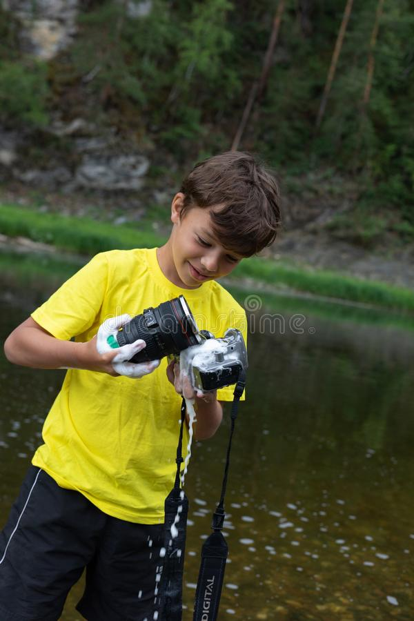 Un garçon de 9 ans tient une caméra de savon et une éponge dans des ses mains mal nettoyage de la caméra et de la lentille photo libre de droits