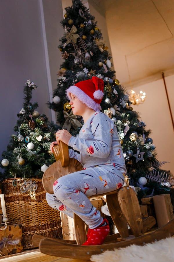 Un garçon de huit ans portant un chapeau de Père Noël et un pyjama monte à cheval en bois photographie stock libre de droits