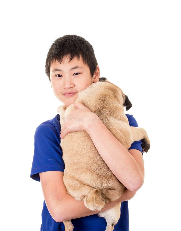 Un garçon de l'adolescence retenant son crabot photo libre de droits