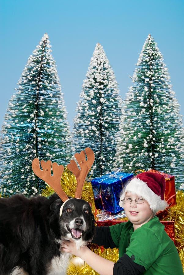 Un garçon de Noël et son crabot de renne photos stock