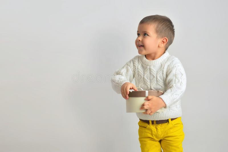 Un garçon de sourire agitated est ouvert un cadeau d'une boîte en carton attachée images stock
