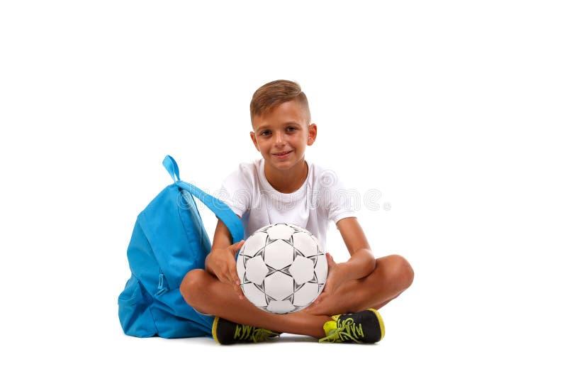 Un garçon de sourire avec une boule et un sac bleu se reposant dans un yoga posent Enfant heureux d'isolement sur un fond blanc s photo libre de droits