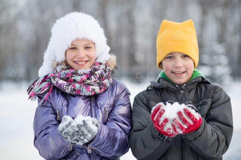 Un garçon de sourire avec une fille jouant avec des boules de neige photos stock