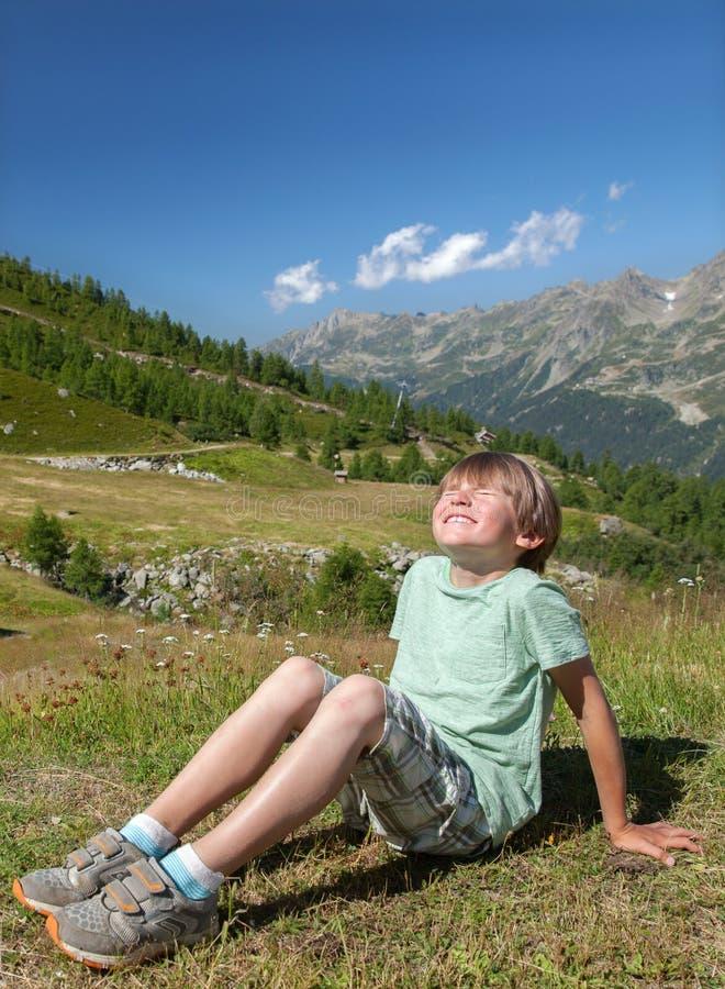 Un garçon de sourire s'assied sur la pente en montagnes images stock