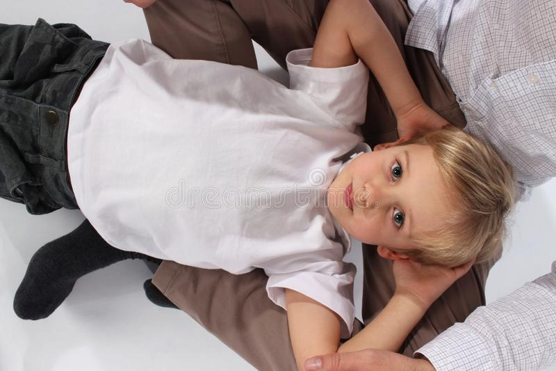 Un garçon doux adorable se situant dans le recouvrement de son papa photos stock