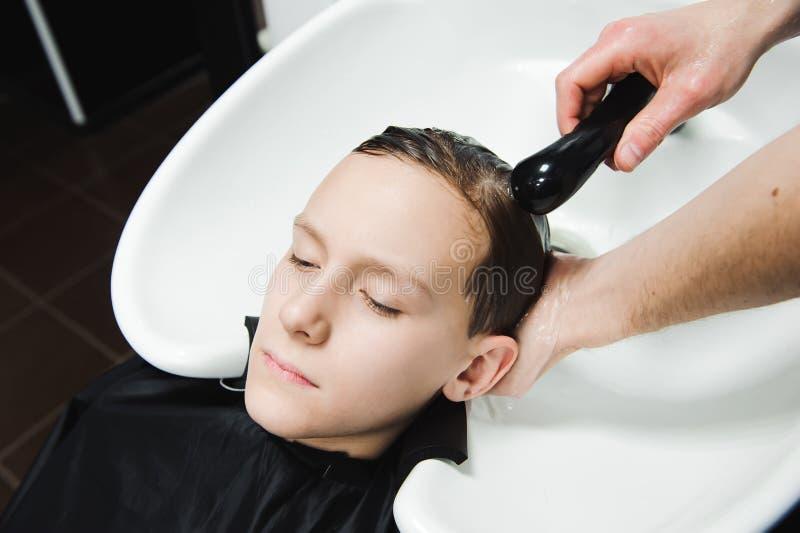 Un garçon est lavé par le coiffeur dans le raseur-coiffeur image stock