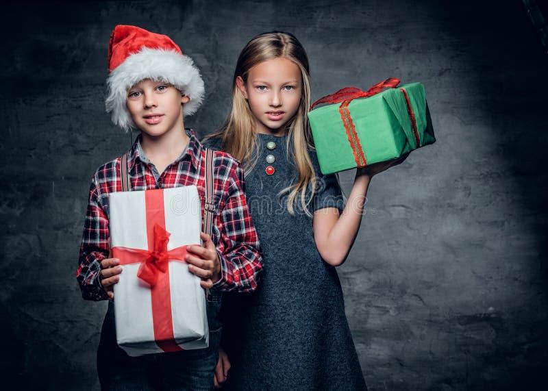 Un garçon et une fille blonde tient des boîte-cadeau photographie stock libre de droits
