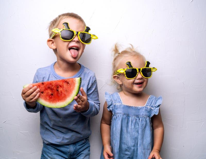 Un garçon et une fille heureux dans des lunettes de soleil jaunes mangent une pastèque rouge mûre sur une fan blanche de mur Port photo stock