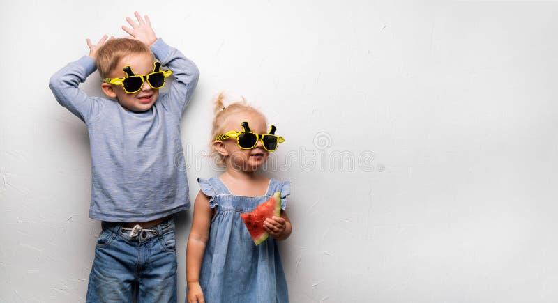 Un garçon et une fille heureux dans des lunettes de soleil jaunes mangent une pastèque rouge mûre sur une fan blanche de mur Port images stock