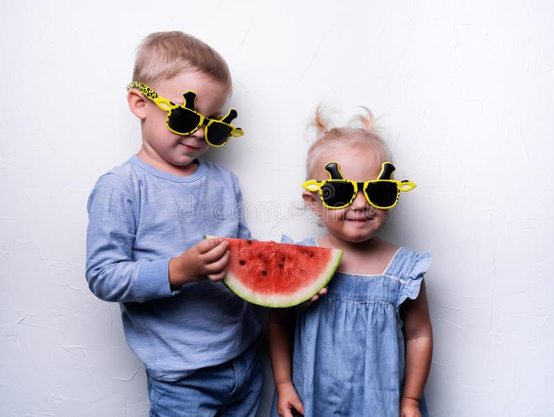 Un garçon et une fille heureux dans des lunettes de soleil jaunes mangent une pastèque rouge mûre sur une fan blanche de mur Port photographie stock