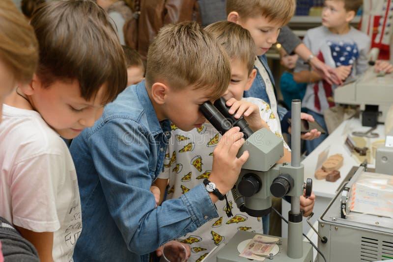 Un garçon examine une vieille facture dans un musée par un microscope image stock