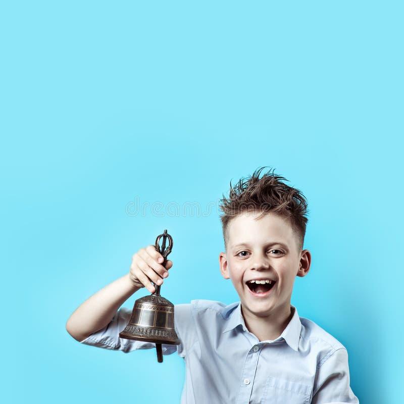 Un garçon heureux dans la chemise légère va instruire Il a une cloche dans sa main, qu'il sonne et sourit images libres de droits