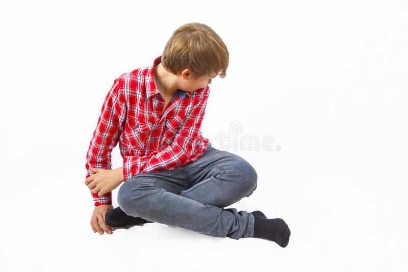Un garçon intelligent assis par terre images libres de droits