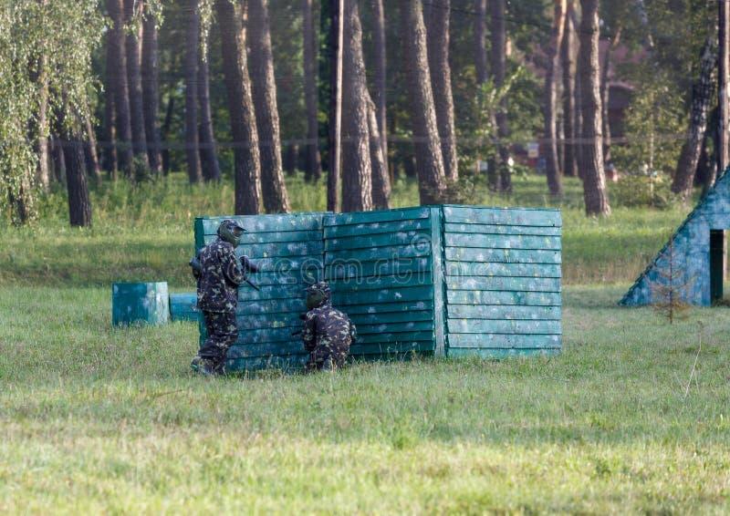 Un garçon joue au paintball sur le champ deux équipes de joueurs de paintball sous la forme de camouflage avec des masques, casqu photographie stock libre de droits