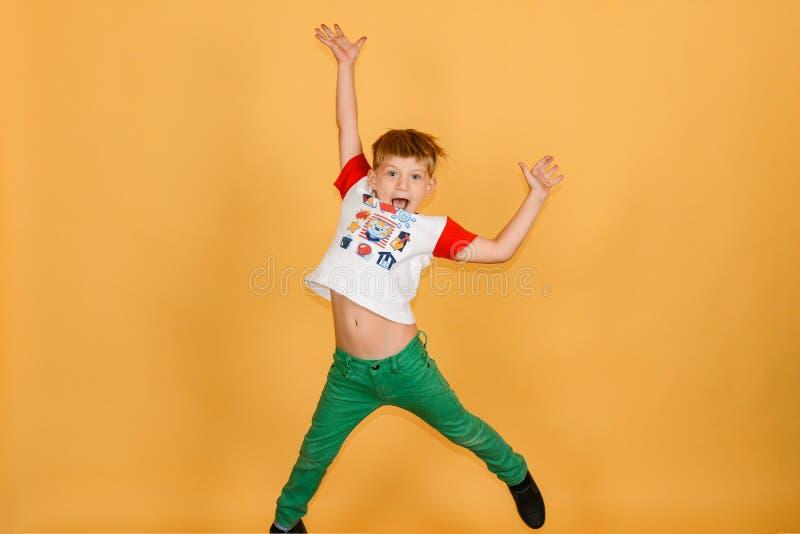 Un garçon joyeux et joyeux saute sur un fond jaune dans le studio photo libre de droits