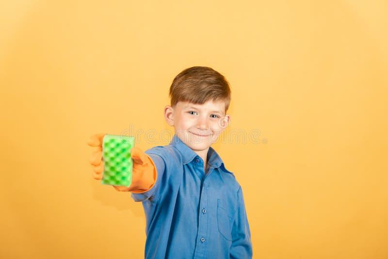 Un garçon joyeux et souriant dans une chemise bleue et des gants oranges montre une éponge de lavage dans le vert sur un fond jau image libre de droits