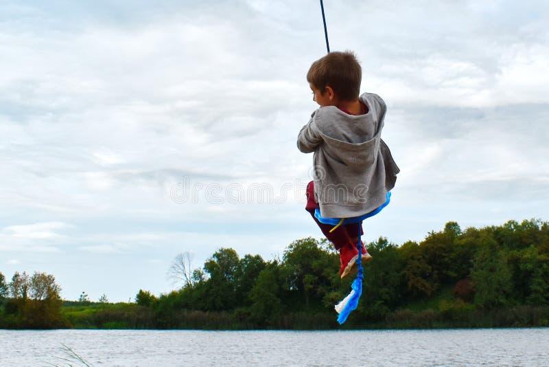 Un garçon joyeux qui balançait sur une corde au-dessus de l'eau image libre de droits