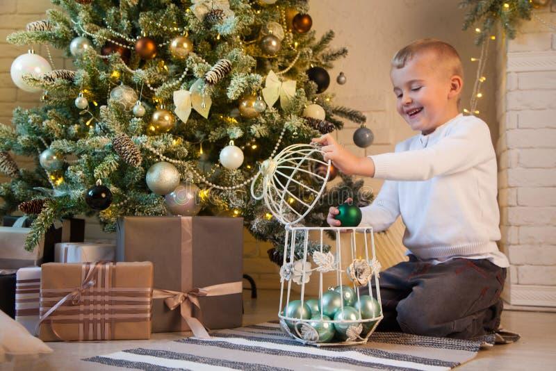 Un garçon mignon de sourire décore l'arbre avec le vert, boules en bon état photographie stock libre de droits