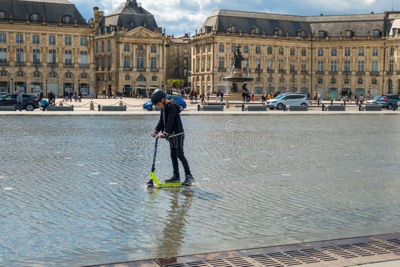 """Un garçon monte un scooter sur le Miroir d """"UCE devant l'endroit de la Bourse en Bordeaux, France photo libre de droits"""