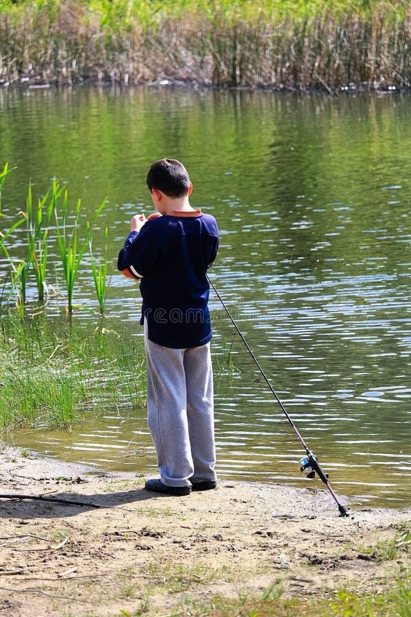 Un garçon obtenant son crochet prêt pour la pêche photos libres de droits